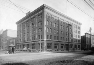 A black and white photo of The Alliance Center and the O'Fallon Supply Building in 1908