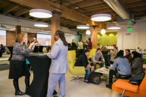 Various groups of people gather and chat at The Alliance Center's Sustainability Center