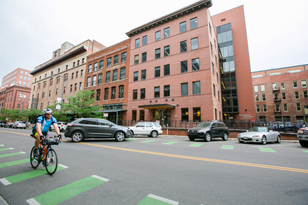 A photo of The Alliance Center from the street view with a man on a bike riding past