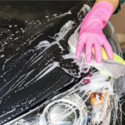 A gloved hand is scrubbing a car clean.