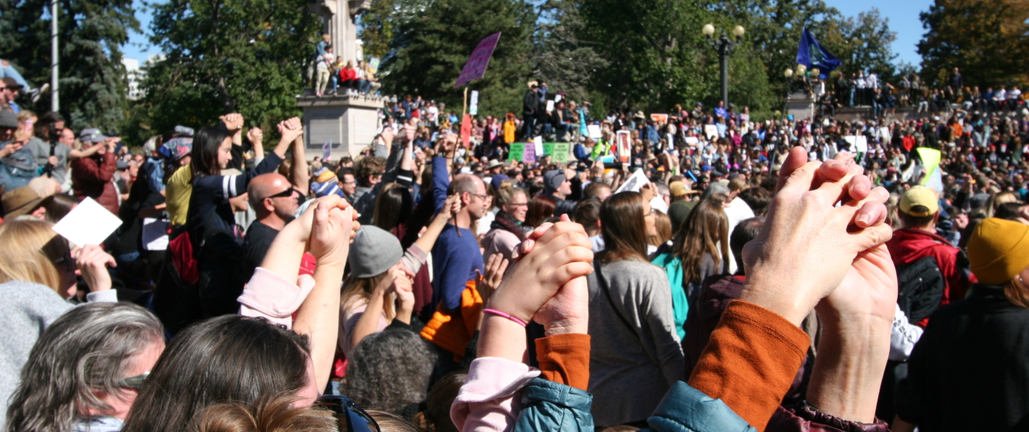 Hundreds of people hold raised hands in Civic Center Park in Denver