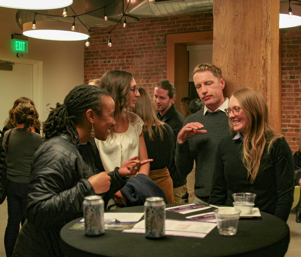 A group of four people chat at an event at The Alliance Center