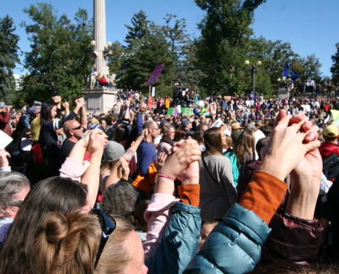 People at the Denver Climate Rally join hands and raise them in the air at Civic Center Park