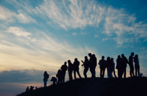 A silhouetted group stands on a hillside at sunset