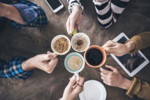 People cheers with coffee mugs