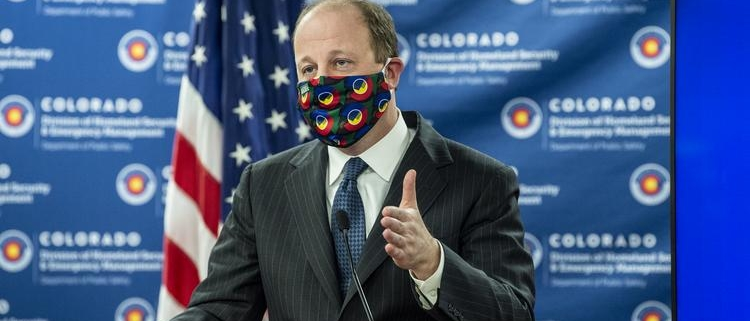 Governor Polis speaks in front of Colorado backdrop with Colorado mask on.