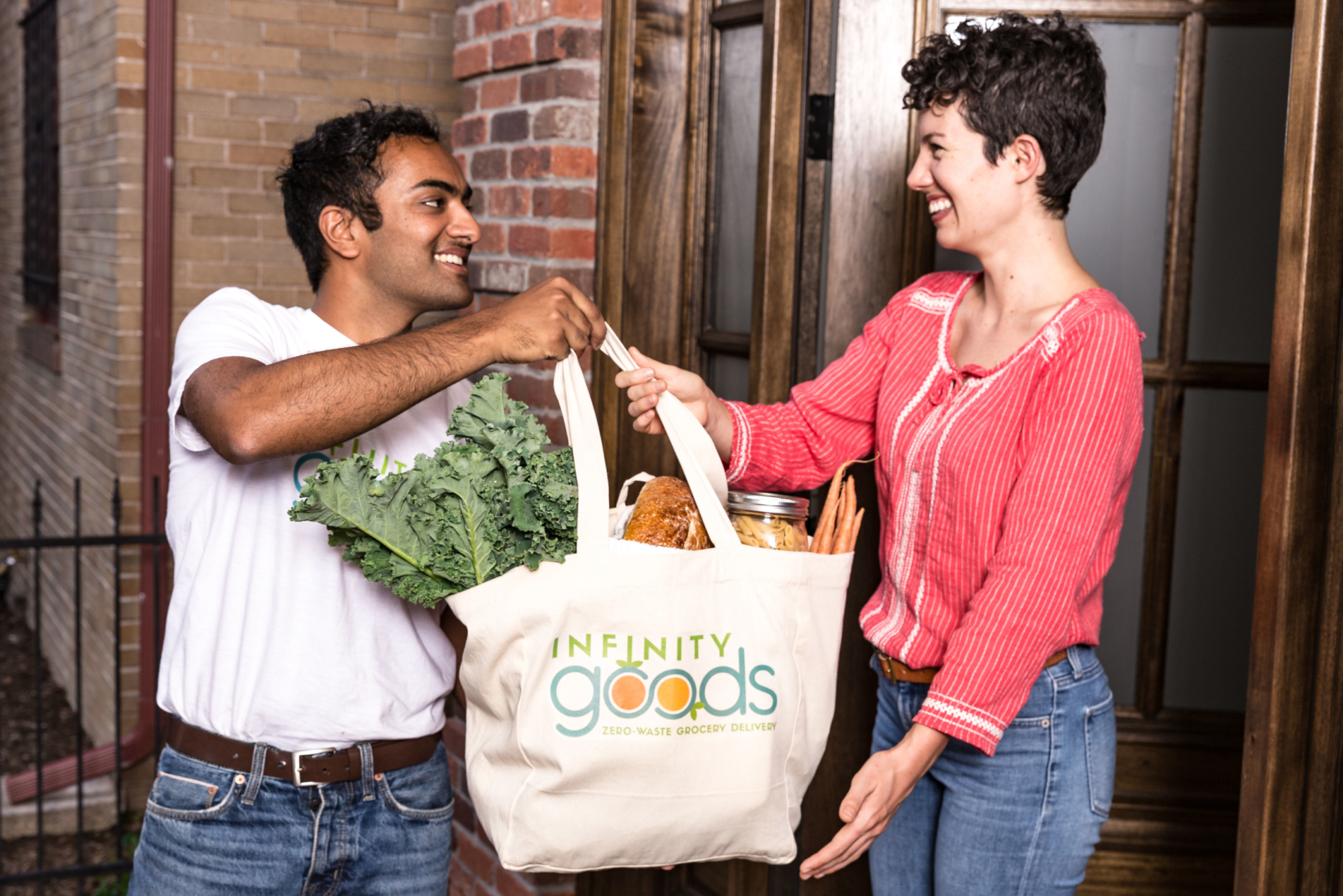Smiling man hands woman bag of goods from Infinity Goods