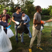 Group of people are volunteering and picking up trash with gloves while two men shake hands in the foreground.