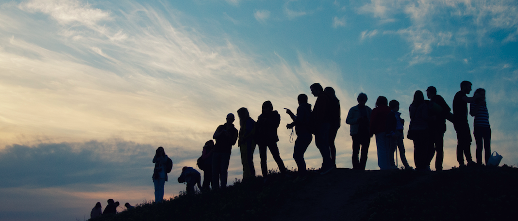 A group of people stand on a hillside at sunset and are silhouetted in the foreground.