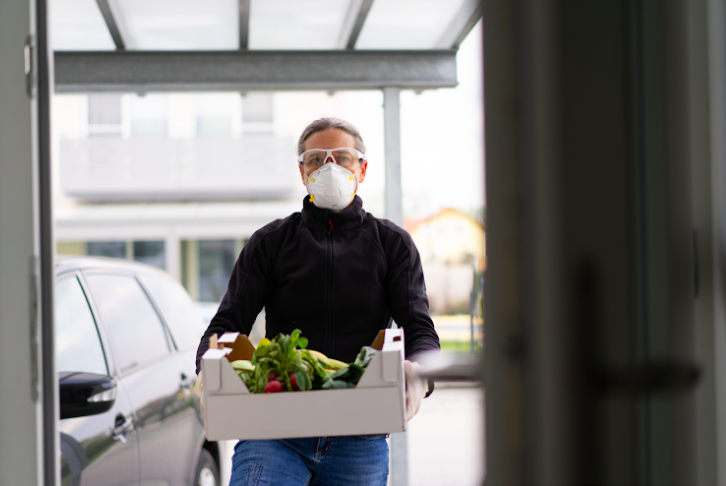 Person with a mask on walks in a building delivering a box of food.