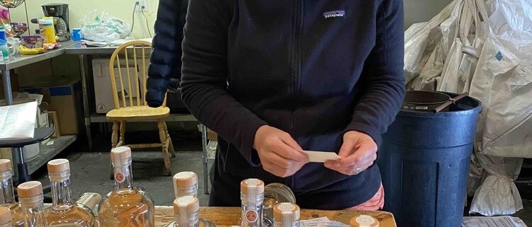 A woman labels bottles of sanitizer at Montanya Distillers