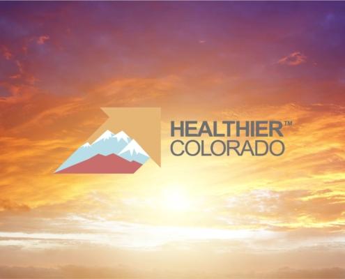 Logo for Healthier Colorado against a sky.