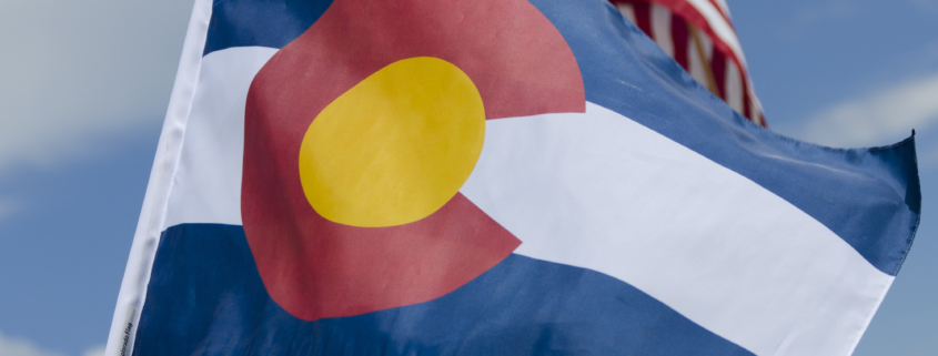 2020 ballot stances. A close up shot of the state flag of Colorado waving in a breeze, with the American flag in the background.