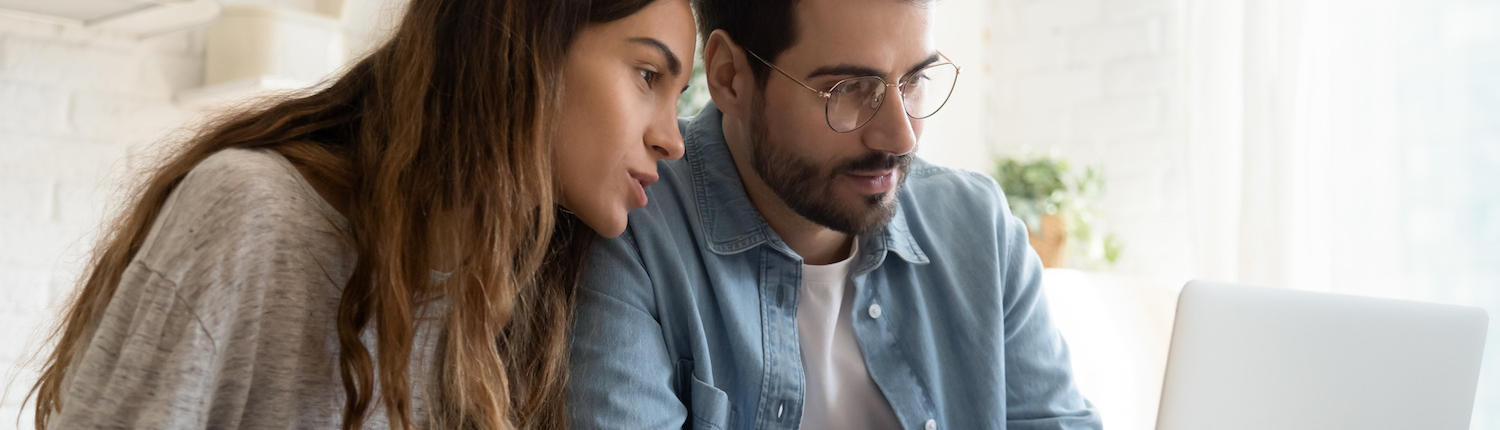 A brunette woman and a brunette man wearing glasses stare at the same computer screen together.