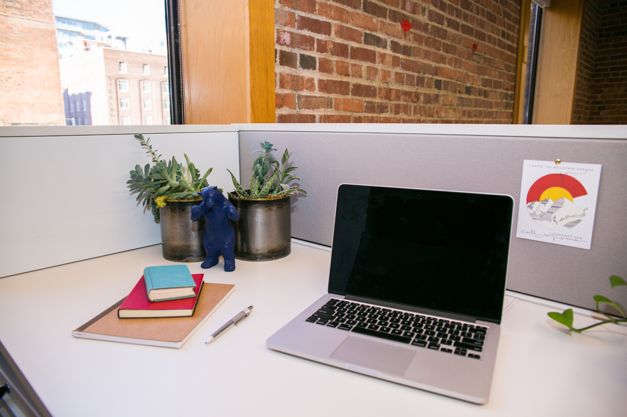 Coworking desk space with laptop, plants and books for tenants