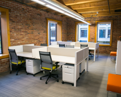 A room with red brick walls, four windows, and wooden ceilings filled with many empty desks.