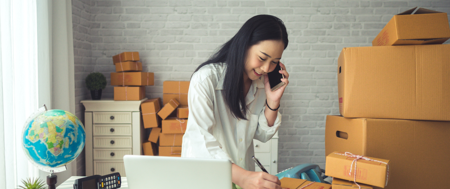 Young woman with dark hair takes orders on a phone and simultaneously takes notes with open laptop on desk and pile of boxes in background.