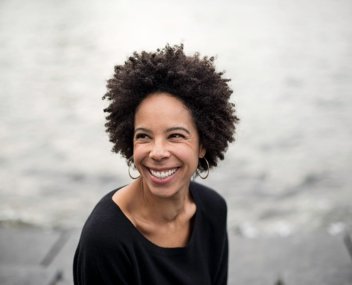 A woman with dark curly hair wearing gold hoop earrings smiles into the distance with a gray blurry background.
