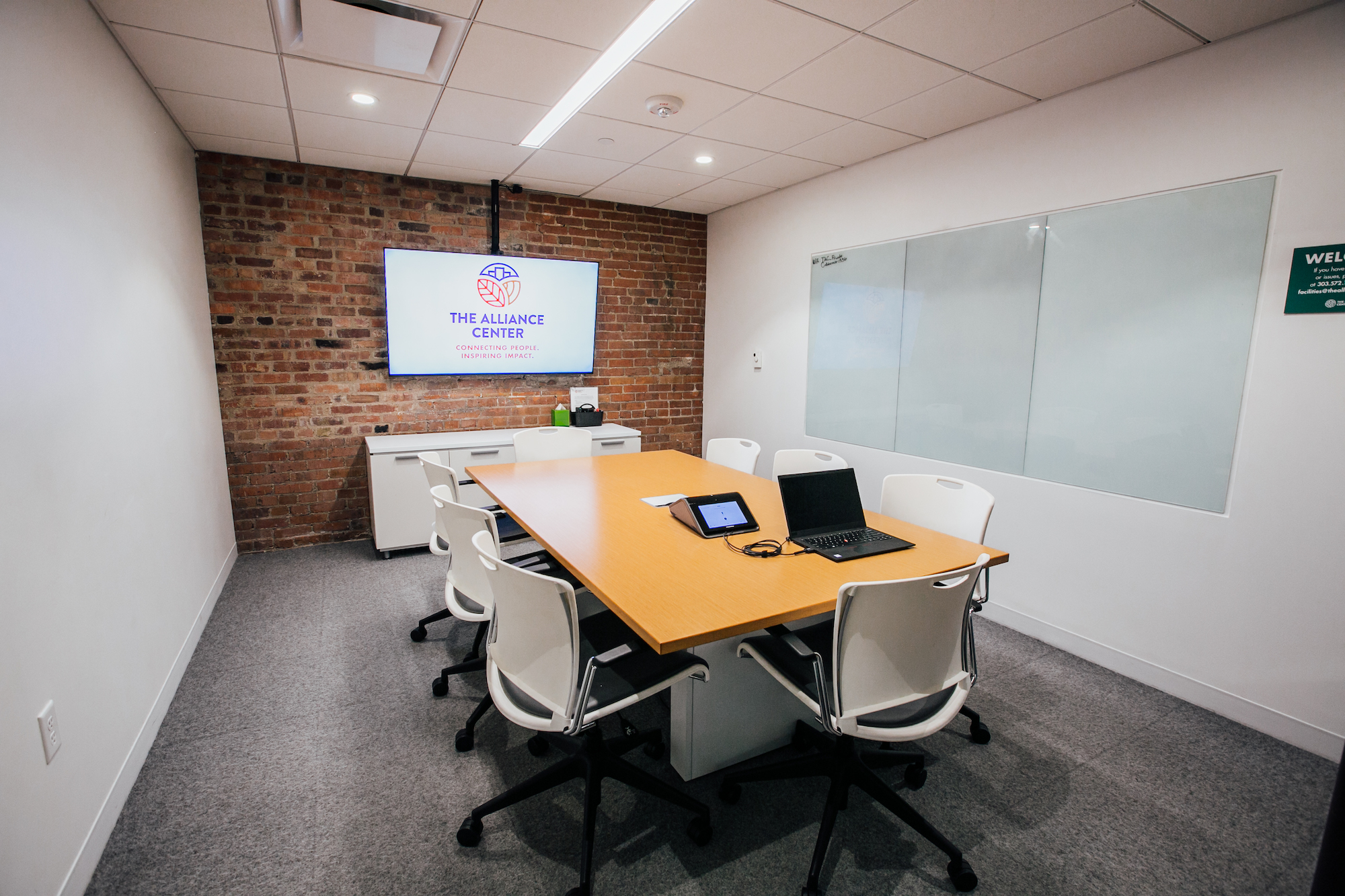 A room with two white walls, an exposed brick wall where a television screen is mounted, and an empty conference table.