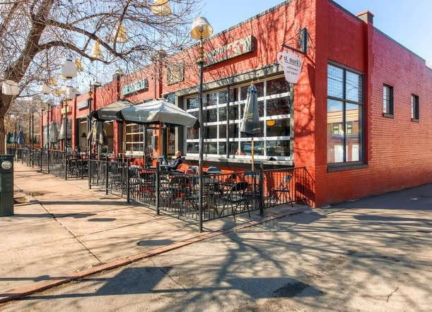 exterior of st. mark's coffee house, patio, with black tables and chairs, red building