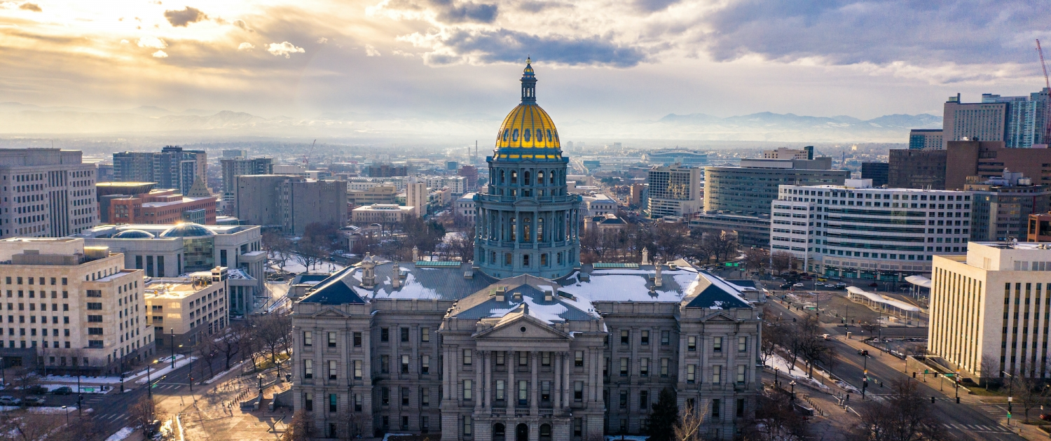 An aerial shot of the Denver capitol building with snow on the ground and the sun setting in the background.