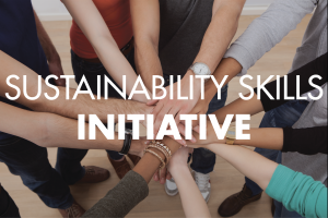 """An overhead shot of people with varying skin tones standing in a circle, extending their arms and piling their hands on top of each other with the text """"Sustainability Skills Initiative"""" overlaid on top of the image."""