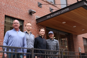 Four men standing shoulder to shoulder in front of the entrance to The Alliance Center.
