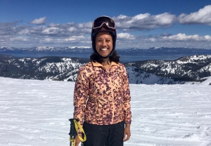 A woman wearing ski goggles and a ski jacket stands on a snowy mountain.