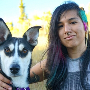 A person with dark hair, blue and pink highlights and a septum piercing sitting next to a dog with plants in the background.