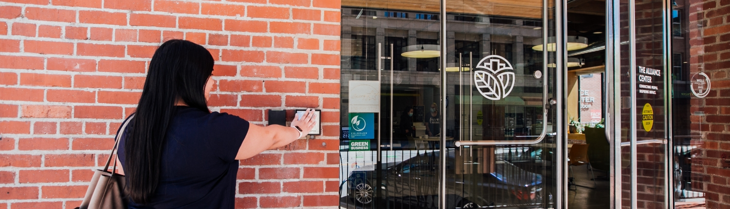 Woman stretches her arm out in front of her to activate a motion sensor device and thereby open a door.
