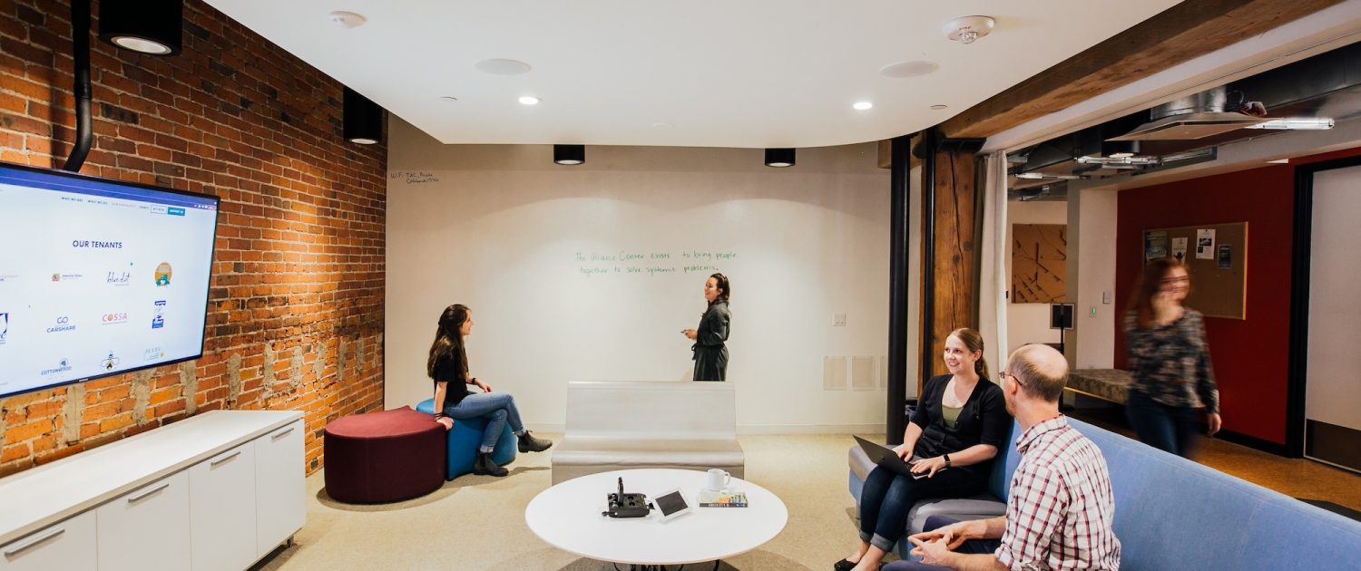 People are working together on a couch in a coworking space while looking at a screen. Two other people in the background are writing ideas on a whiteboard.