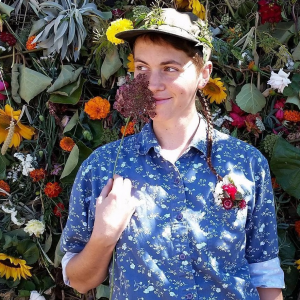 A person in a floral button-up shirt with a green hat on, holding a flower next to their face with other flowers in the background.