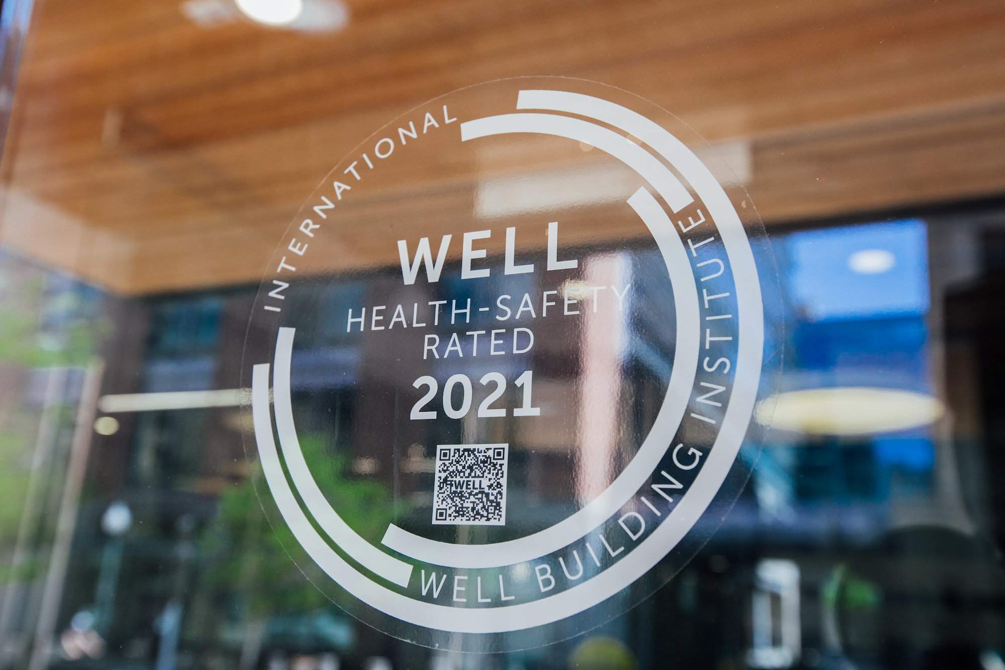 A seal for WELL Health-Safety rating on The Alliance Center's front door.