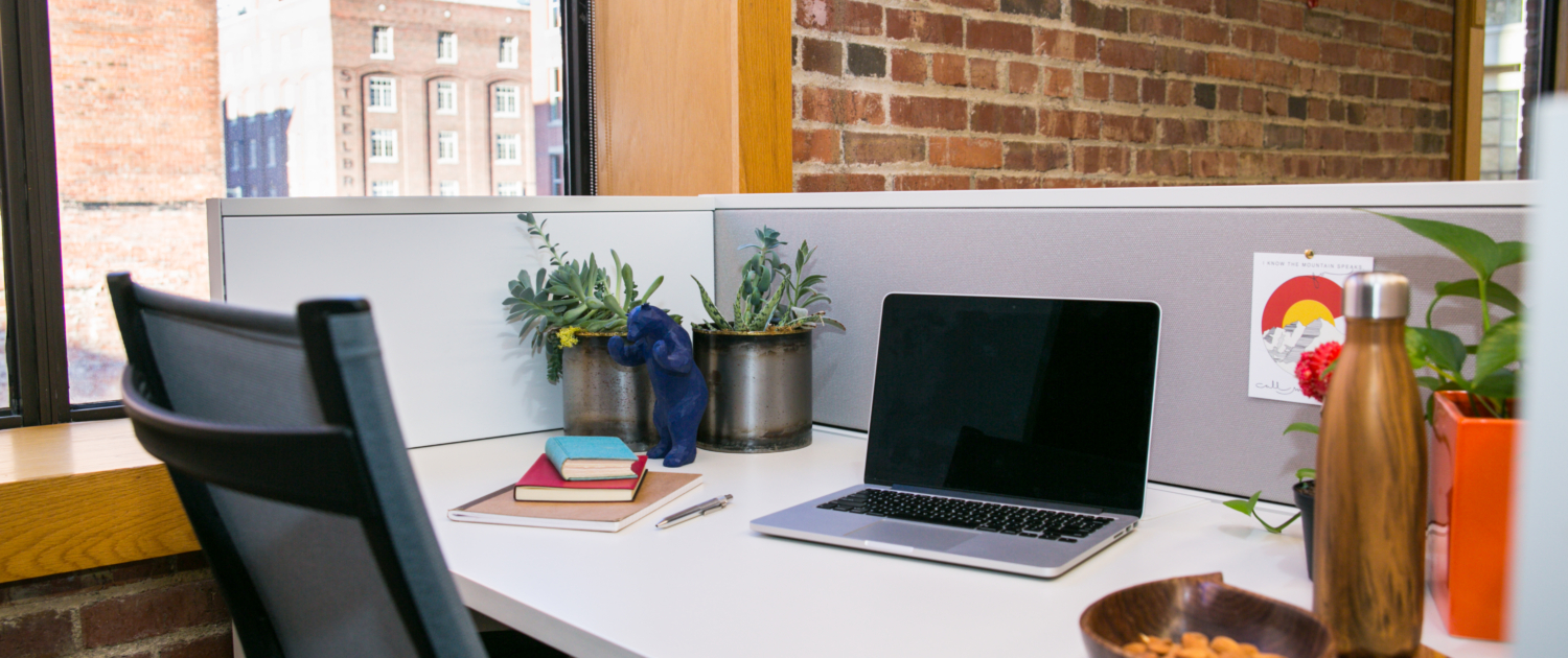 Desk in The Alliance Center building with a laptop, water bottle, notebooks, plants and a snack on it.