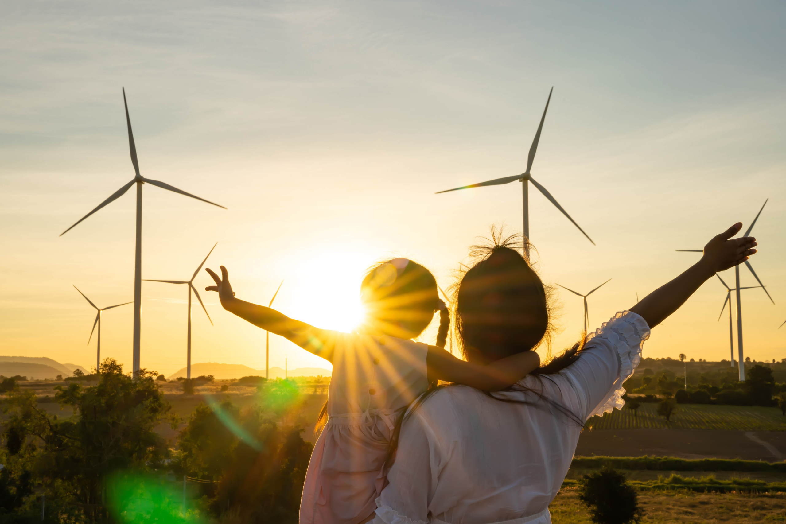 Woman holds child, both look out at sunset against wind turbines, holding hands out with joy.
