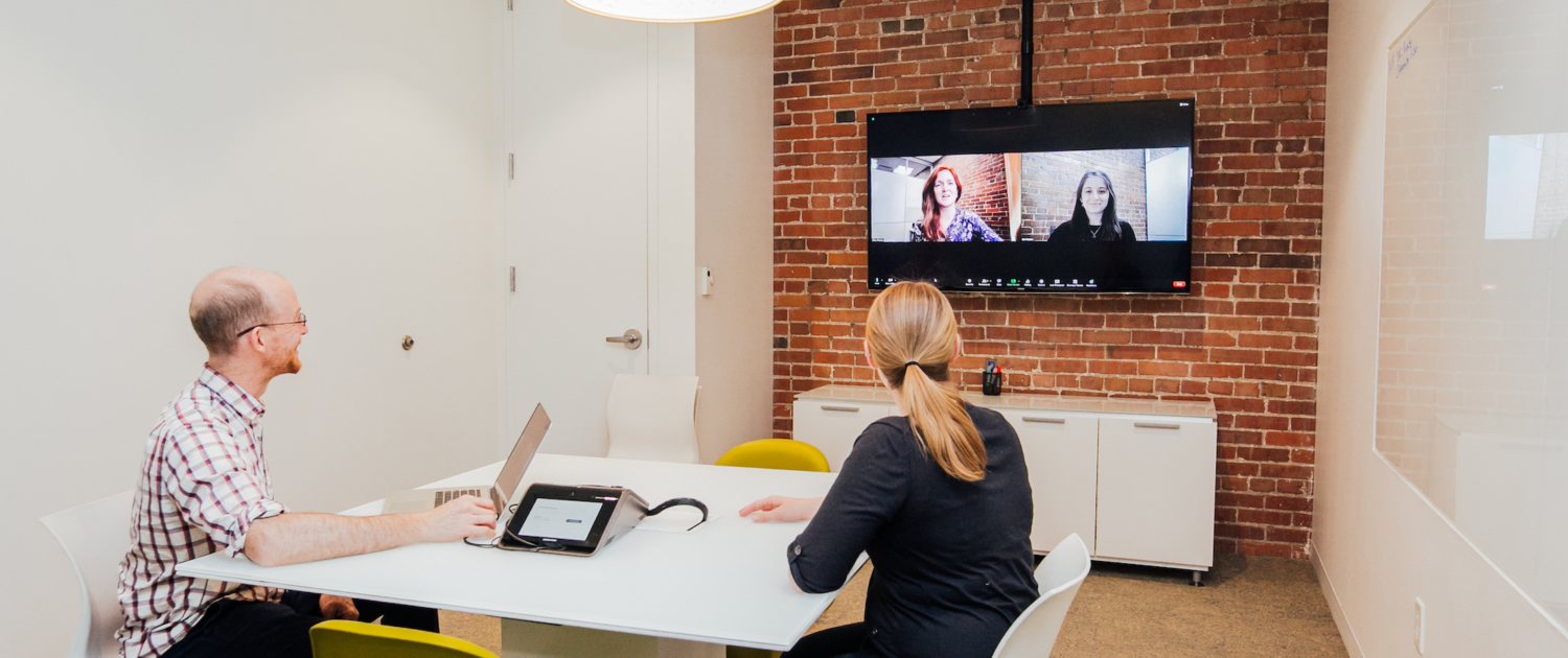 Two people sit at a table in a room with an exposed brick wall where a television screen is mounted and displaying two other people on a video call.
