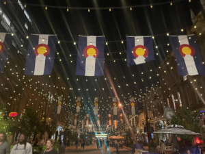 A picture of Larimer Square decorated with lights and flags at night